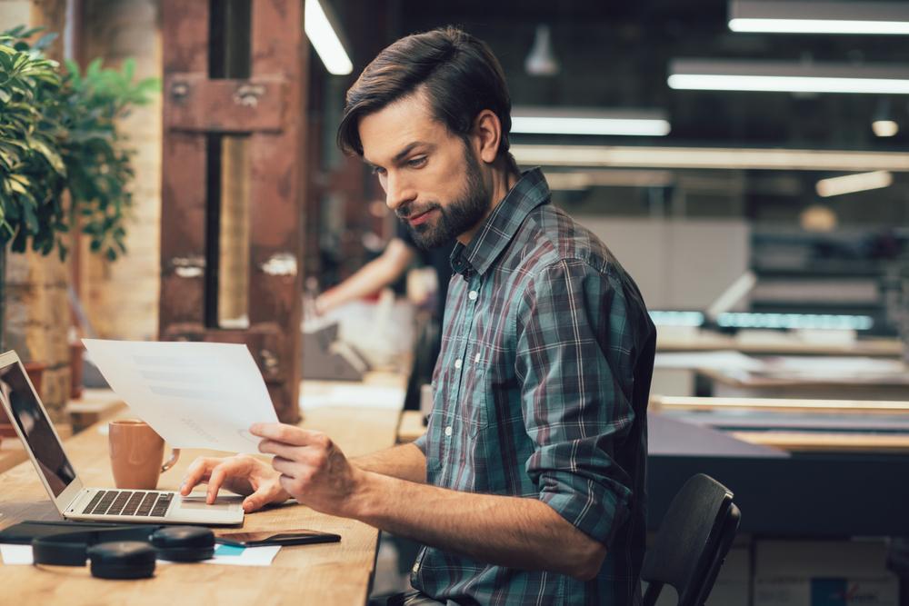 Man schaut auf Zettel, Mann schaut auf sein Arbeitszeugnis, Arbeitszeugnis Aufbau