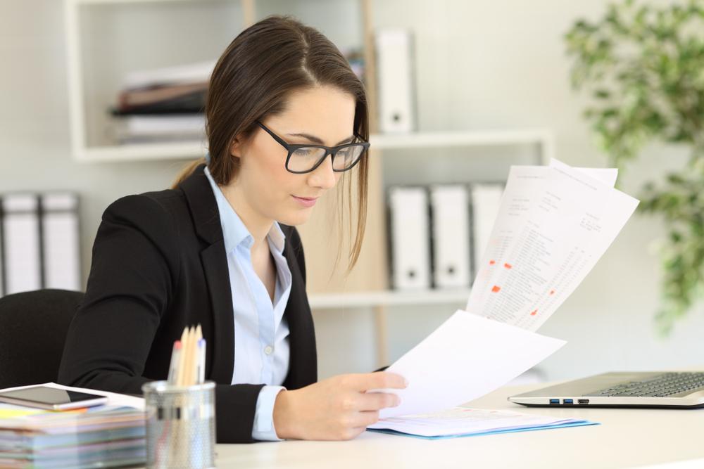 Arbeitszeugnis Azubis, Azubi weiblich schaut auf ihr Arbeitszeugnis