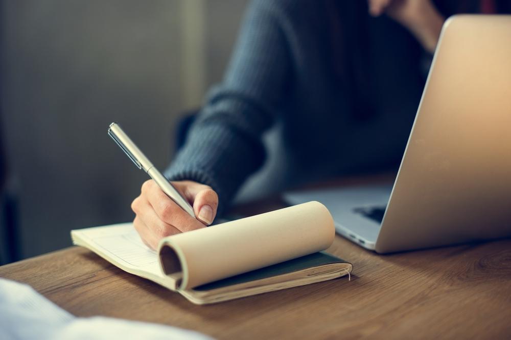 Beurteilung schreiben, Hand Block schreiben, Person am Laptop