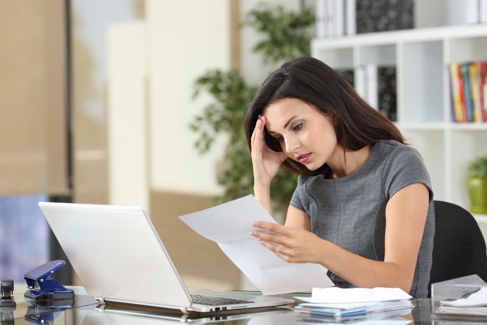 Arbeitszeugnis Noten, Zeugnissprache verstehen, Frau schaut unsicher auf Zettel