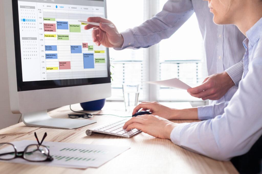 Gleitzeitmodelle Vorteile und Nachteile, Arbeitszeit neu planen, Organisation der Mitarbeiter zu verschiedenen Arbeitszeiten arbeiten, Mann sitzt am Computer und erstellt einen Arbeitsplan