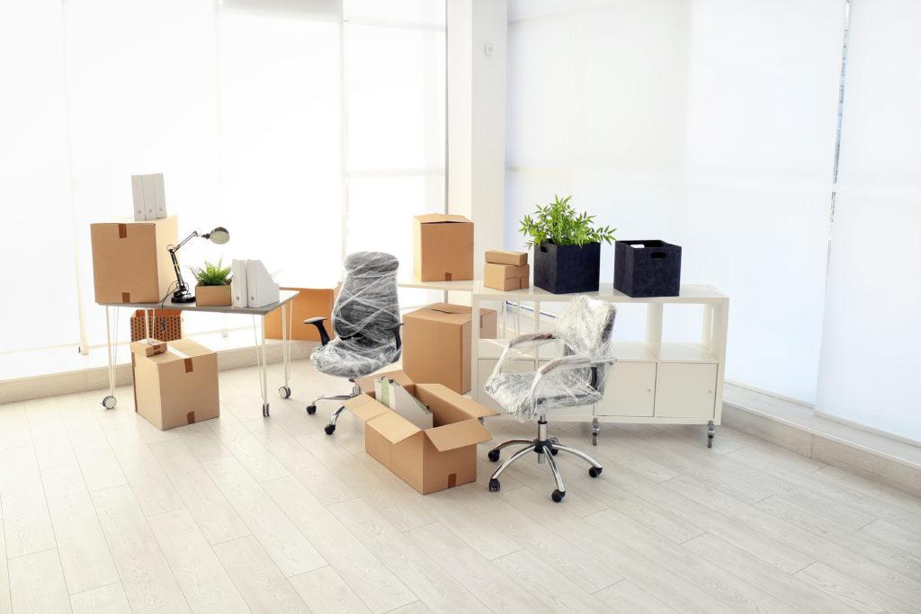 Firmenumzug, Checkliste, gepackte Kartons, Möbel in Schutzfolie